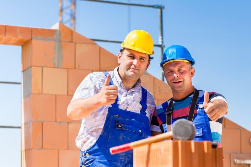 Travailleurs de chantier de construction construisant des murs sur la maison images stock