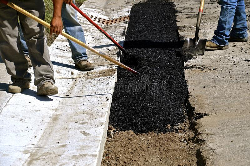 Travailleurs de construction de routes répandant l'asphalte photographie stock libre de droits