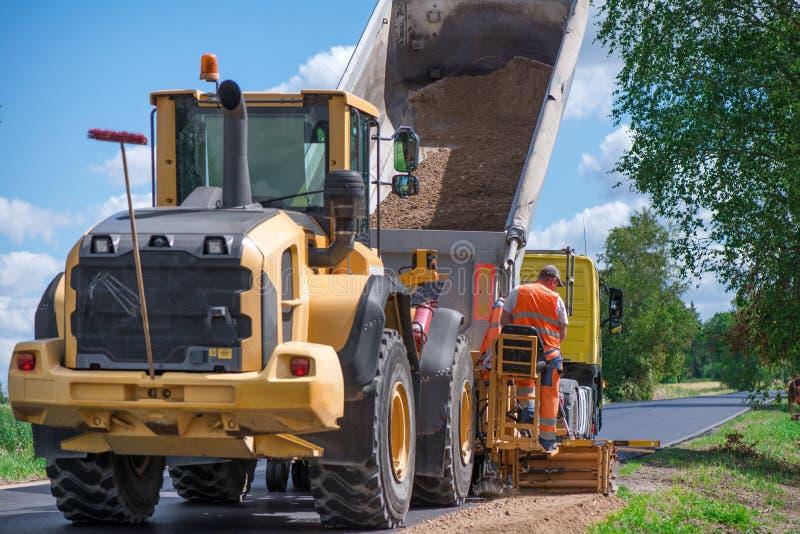 Travailleurs de construction de routes réparant la route de route le jour ensoleillé d'été image libre de droits