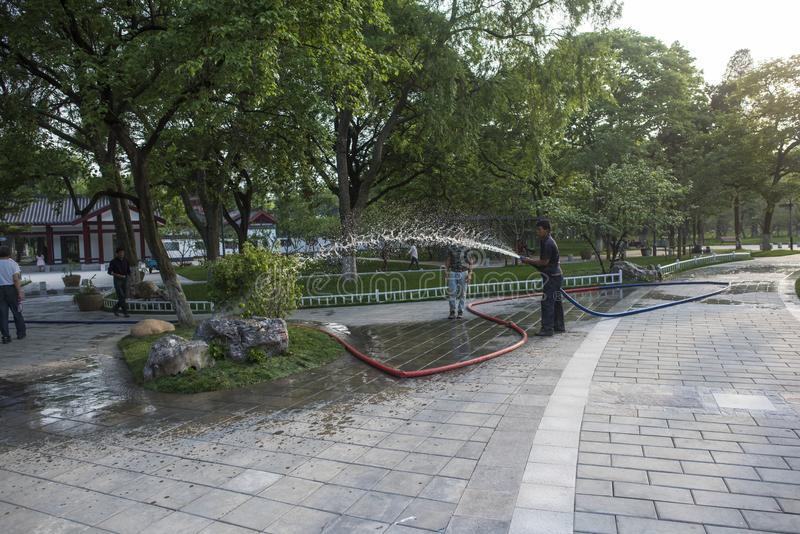 Travailleurs de jardin arrosant des fleurs en parc de lac Xuanwu photographie stock libre de droits