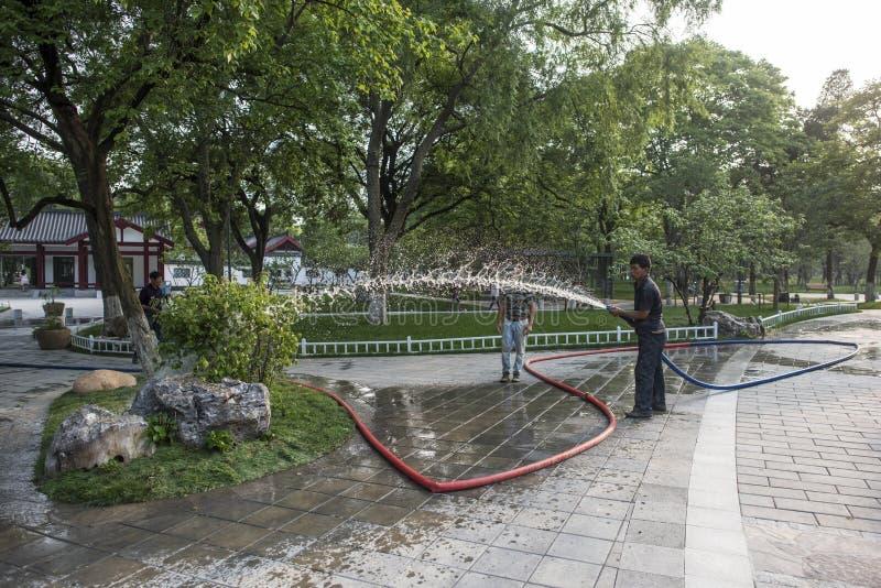 Travailleurs de jardin arrosant des fleurs en parc de lac Xuanwu images libres de droits