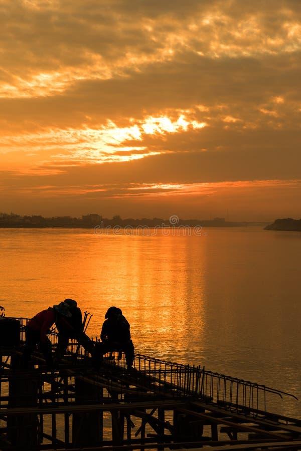 Travailleurs de la construction au-dessus de coucher du soleil photographie stock