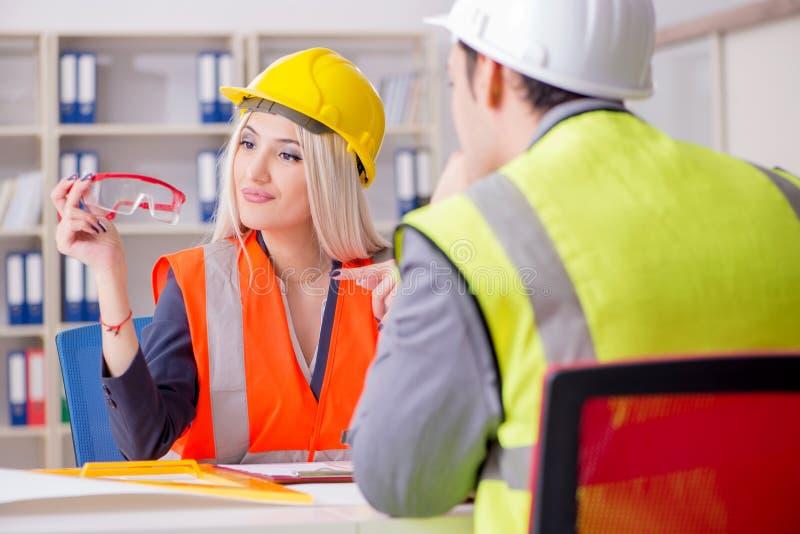 Travailleurs de la construction ayant la discussion dans le bureau avant de commencer photo stock
