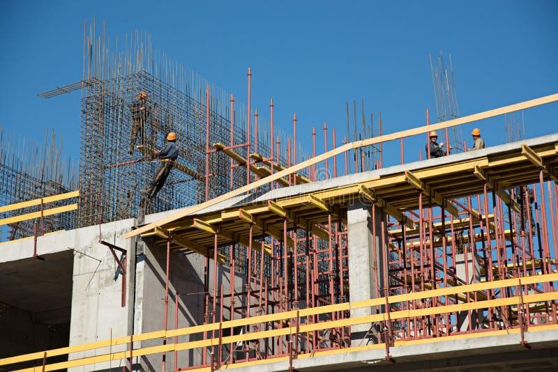 Travailleurs de la construction dans le chantier de construction sur le fond de ciel photo libre de droits