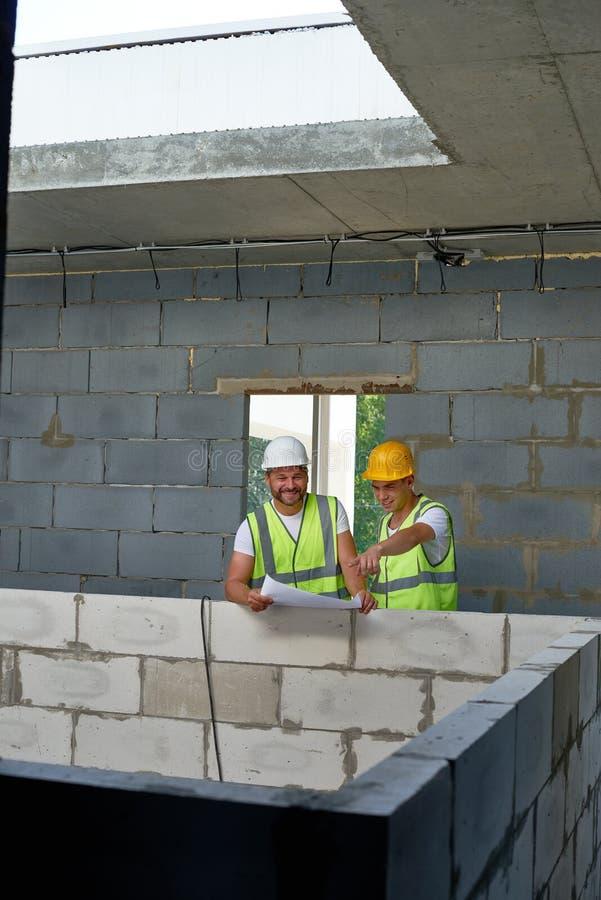Travailleurs de la construction gais sur le site photographie stock
