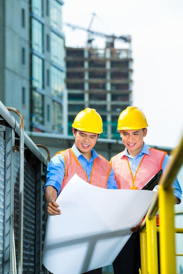 Travailleurs de la construction indonésiens asiatiques sur le chantier photo stock