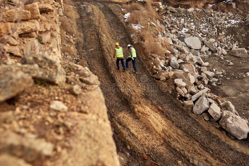 Travailleurs de la construction marchant en saleté sur le site image stock