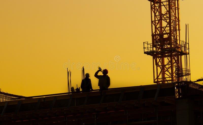 Travailleurs de la construction sur le chantier au coucher du soleil images libres de droits