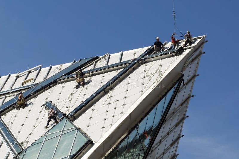 Travailleurs de la construction sur le toit photo stock