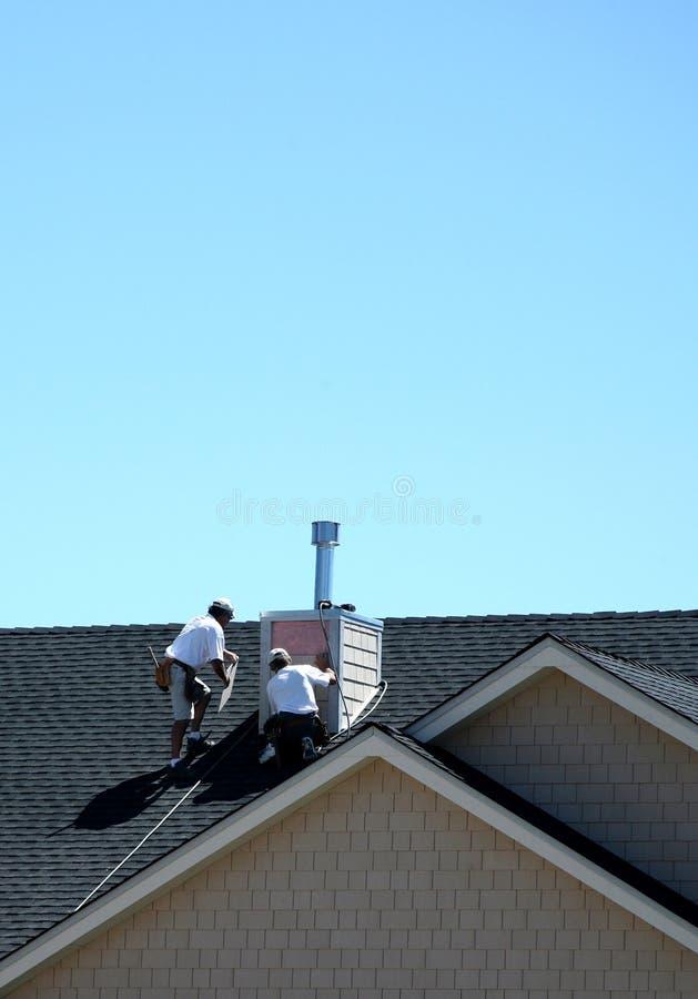 Travailleurs de la construction sur le toit photo libre de droits