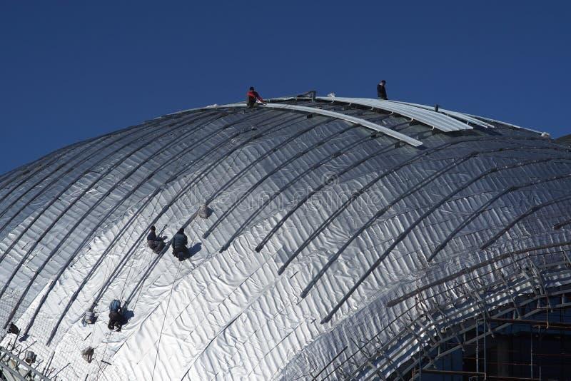 Travailleurs de la construction travaillant au toit d'un bâtiment attaché avec image stock