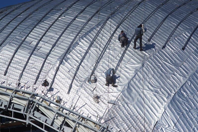 Travailleurs de la construction travaillant au toit d'un bâtiment attaché avec photographie stock libre de droits
