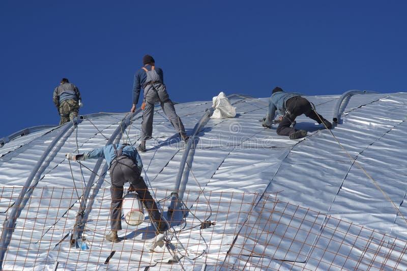 Travailleurs de la construction travaillant au toit d'un bâtiment attaché avec photographie stock