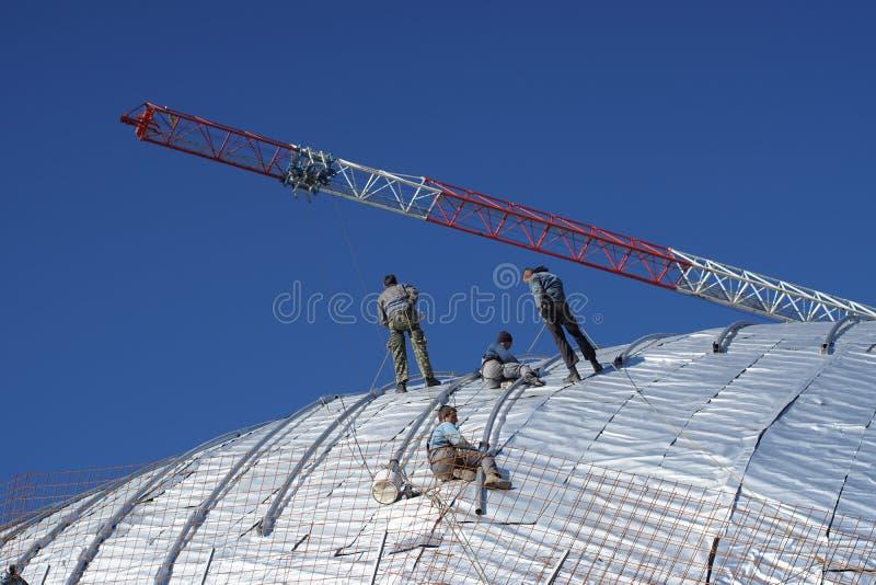 Travailleurs de la construction travaillant au toit d'un bâtiment attaché avec photos stock