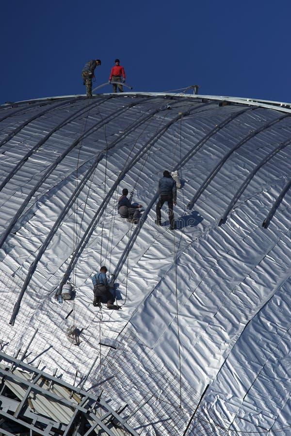 Travailleurs de la construction travaillant au toit d'un bâtiment attaché avec photos libres de droits