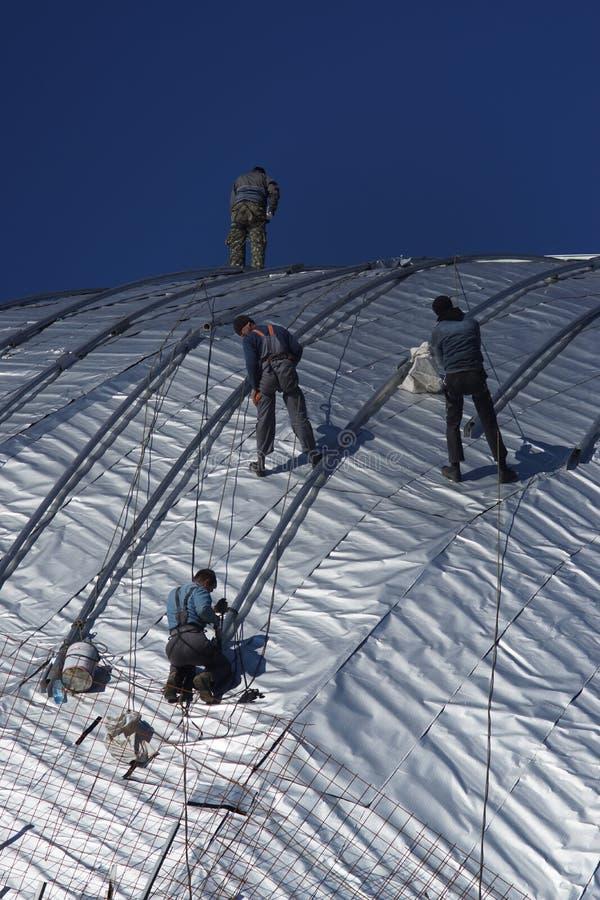 Travailleurs de la construction travaillant au toit d'un bâtiment attaché avec images stock