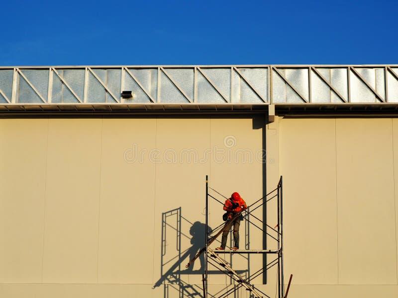Travailleurs de la construction travaillant ? l'?chafaudage photographie stock libre de droits