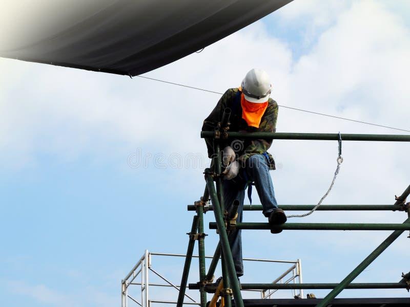 Travailleurs de la construction travaillant ? l'?chafaudage photos stock