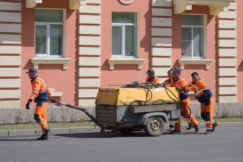 Travailleurs de route - les travailleurs migrants ont roulé le vieux compresseur photo libre de droits