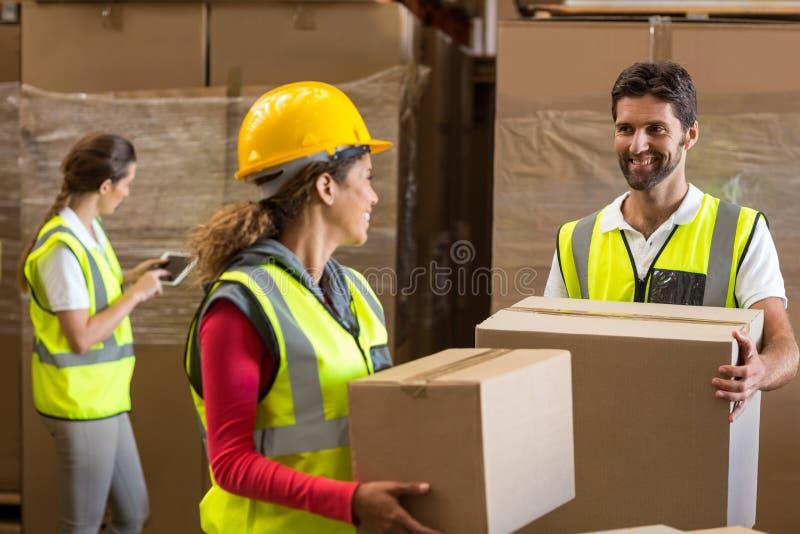 Travailleurs de sourire d'entrepôt portant une boîte en carton photo stock
