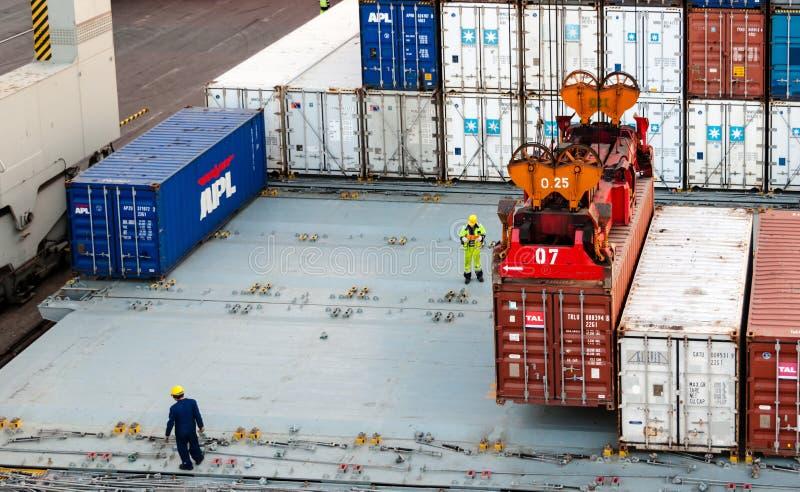 Travailleurs dirigeant le récipient télécharger au dock photographie stock