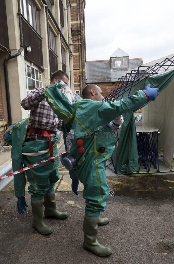 Travailleurs enlevant des costumes de décontamination photo stock