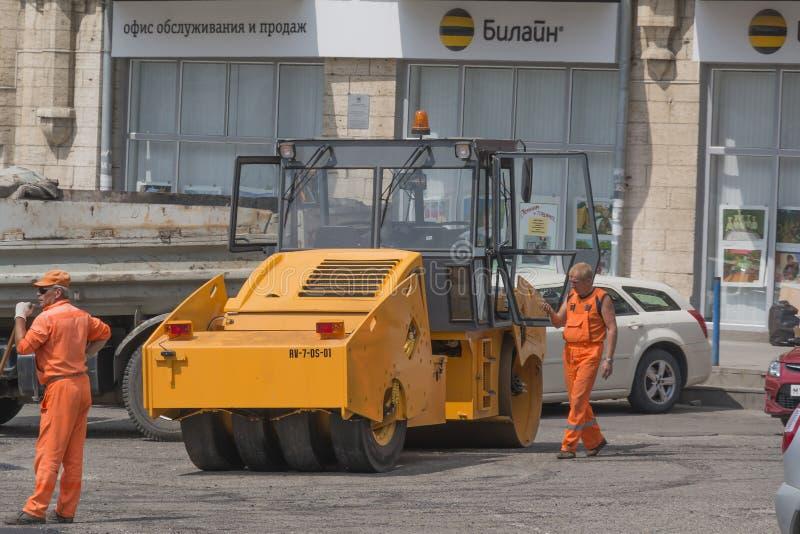 Travailleurs et rouleau d'asphalte, réparation de route photographie stock libre de droits