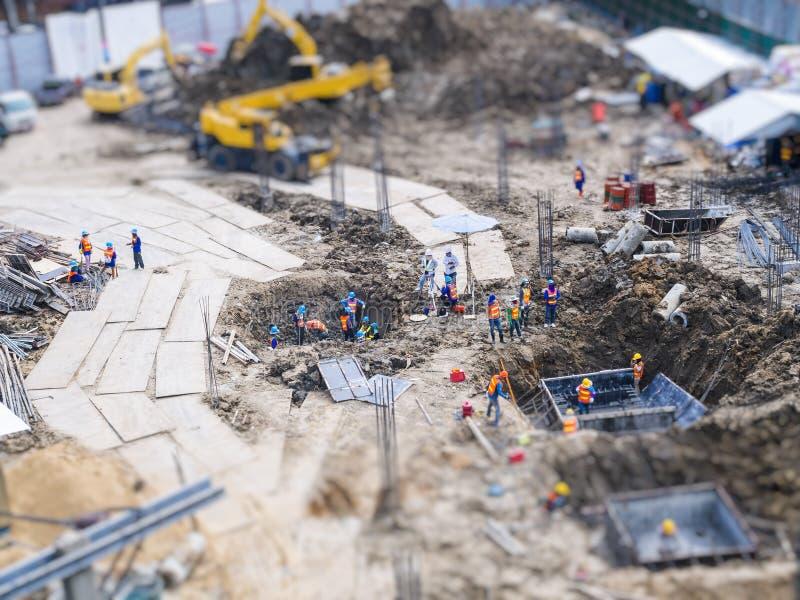 Travailleurs extérieurs de chantier de construction travaillant l'équipement arrière de houe photo stock