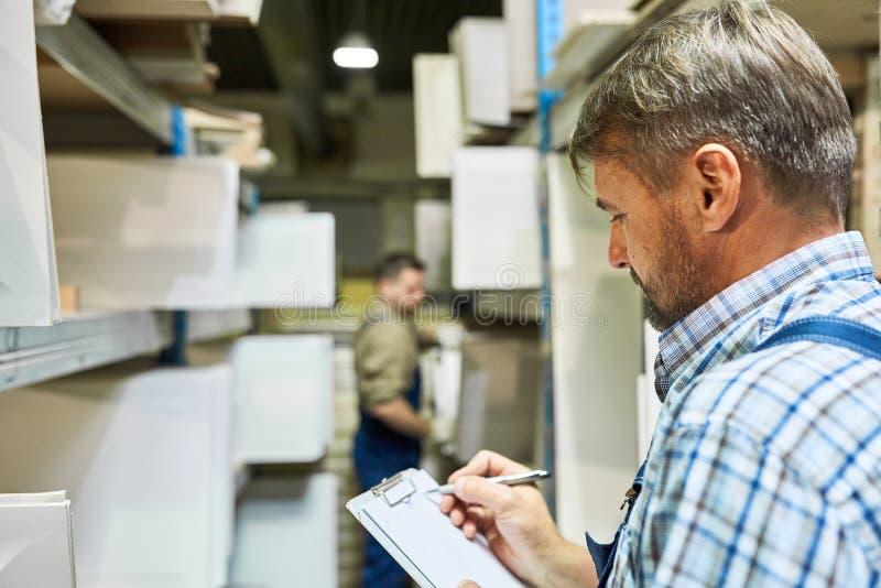 Travailleurs faisant l'inventaire dans le stockage image stock