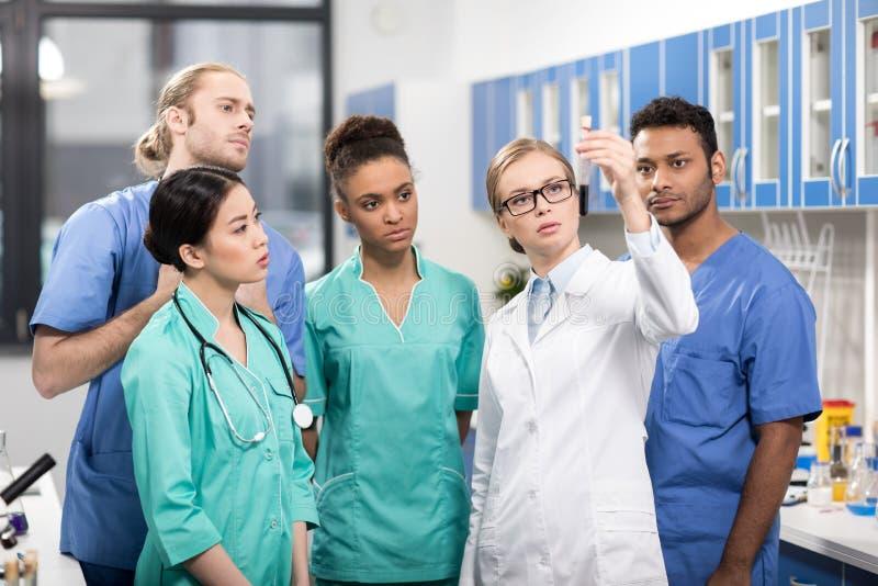 Travailleurs médicaux analysant le tube à essai dans le laboratoire photographie stock libre de droits