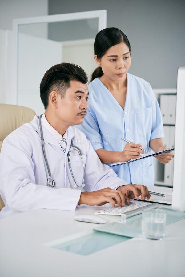 Travailleurs médicaux vérifiant des données sur l'ordinateur photos stock