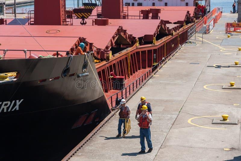 Travailleurs marchant près du grand cargo photo stock