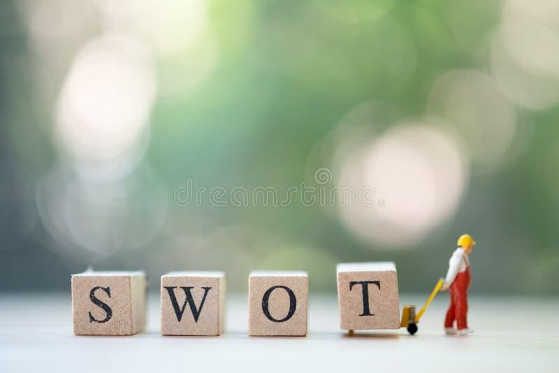 Travailleurs miniatures déplaçant le mot en bois BÛCHEUR image libre de droits