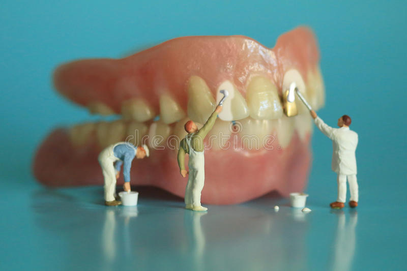 Travailleurs miniatures exécutant des procédures dentaires Bureau dentaire AR photos stock