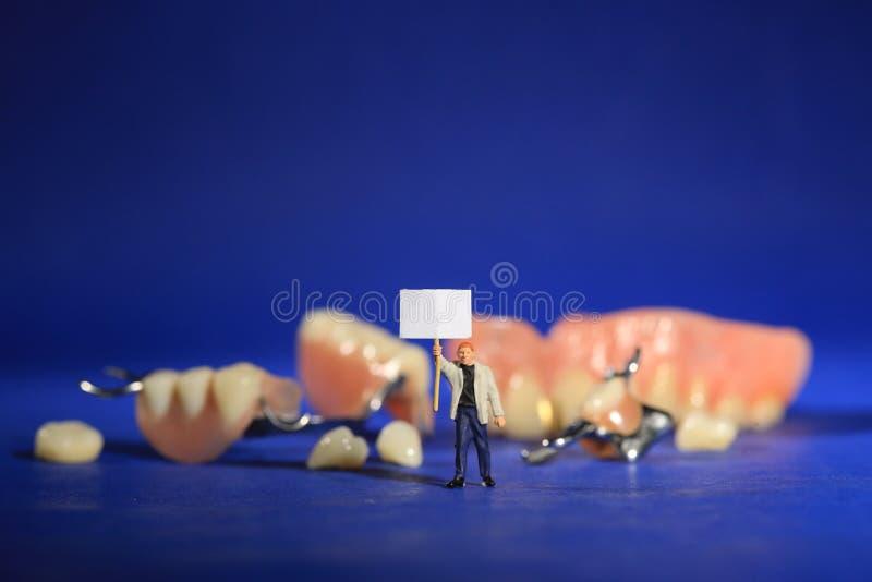 Travailleurs miniatures exécutant des procédures dentaires Bureau dentaire AR images stock