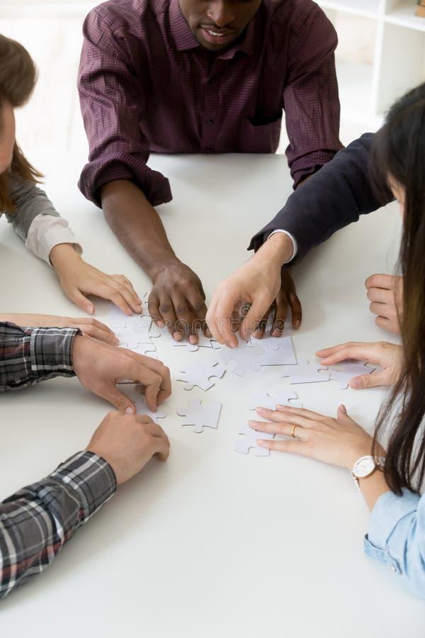 Travailleurs multi-ethniques assemblant le puzzle denteux tout en teambuilding images libres de droits