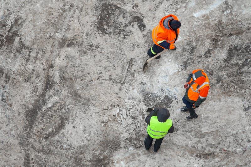 Travailleurs nettoyant la route sale de pelle image libre de droits