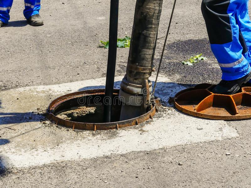 Travailleurs nettoyant les eaux d'égout à une maison residentual photographie stock