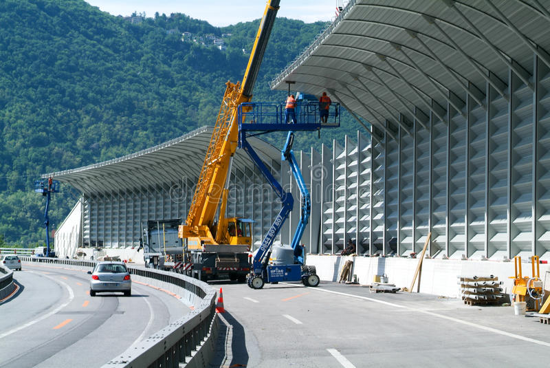 Travailleurs pendant l'installation des barrières de bruit sur la route photos stock