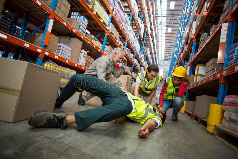 Travailleurs prenant le soin au sujet de leur collègue se trouvant sur le plancher photos libres de droits