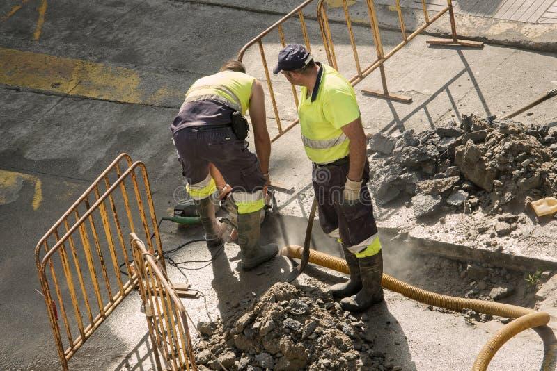 Travailleurs réparant une conduite d'eau cassée sur la route photo libre de droits