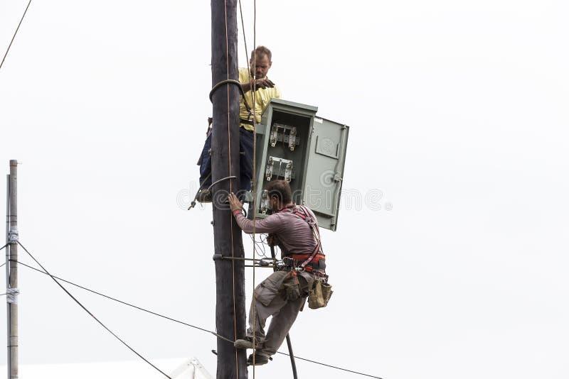 Travailleurs s'élevant sur la ligne de transmission concrète électrique de poteau photos libres de droits