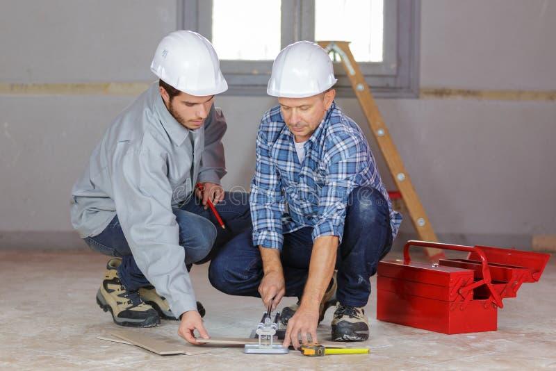 Travailleurs se préparant de niveau à la dalle en béton image stock