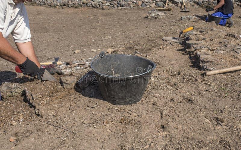 Travailleurs spécialisés creusant avec la truelle sur l'excavation archéologique photos libres de droits