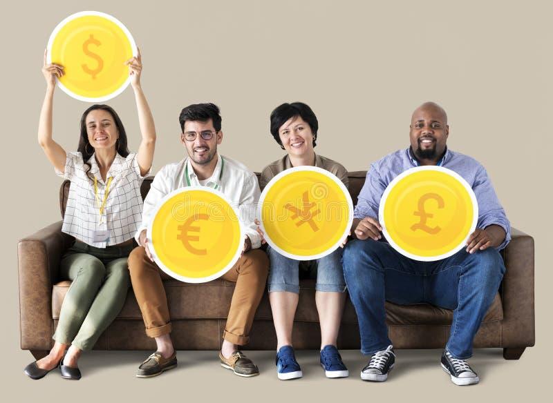 Travailleurs tenant la pièce de monnaie de devise sur le divan photographie stock libre de droits