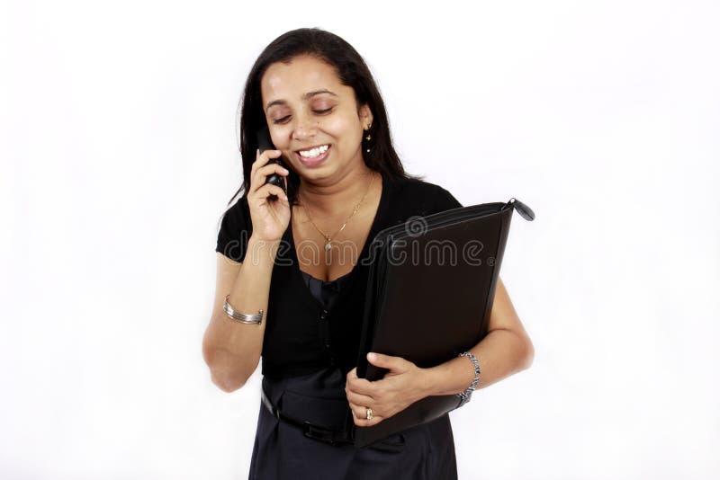 Travailleuse active au téléphone photographie stock