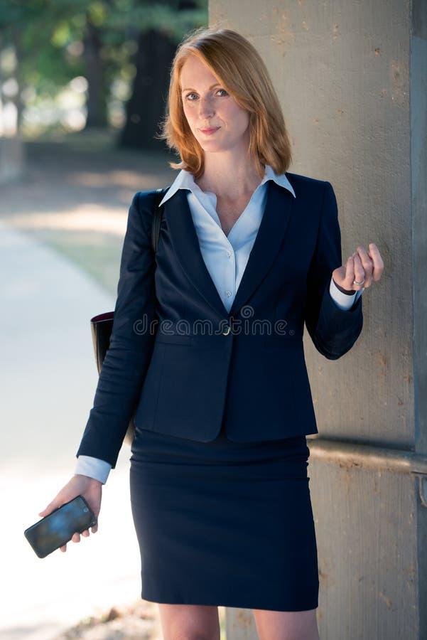 Travailleuse active dans le costume tenant le téléphone portable photos libres de droits
