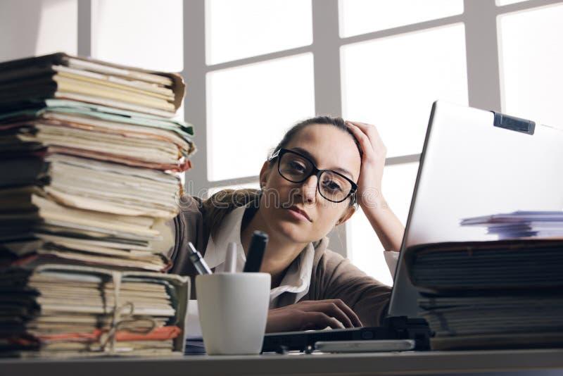Travailleuse active dure avec des fichiers de bureau photo stock