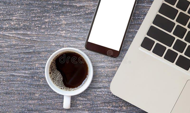 Travaillez le bureau avec l'ordinateur portable et la tasse de café chaude image stock