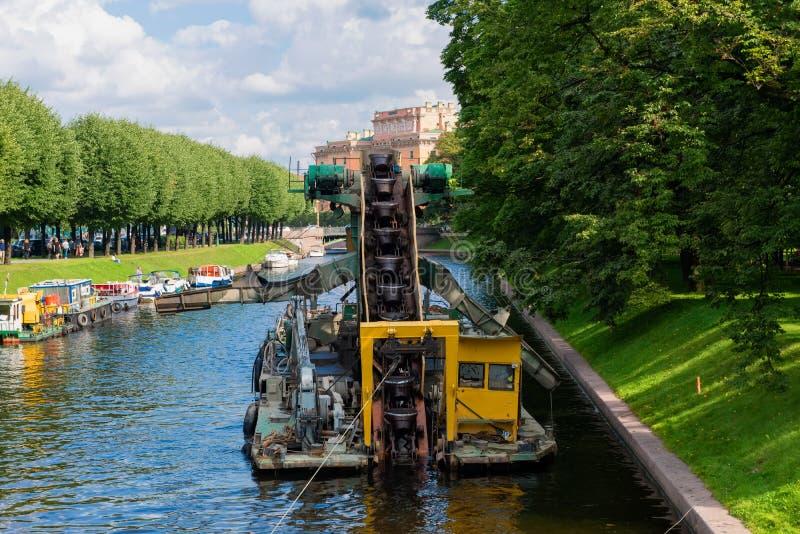 Travaillez pour approfondir le fond dans le canal de la rivière urbaine Moika photo libre de droits